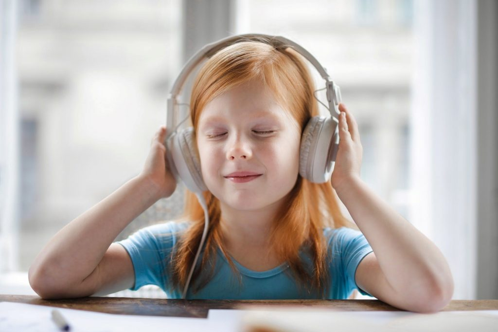 Child wearing headphones and smiling.