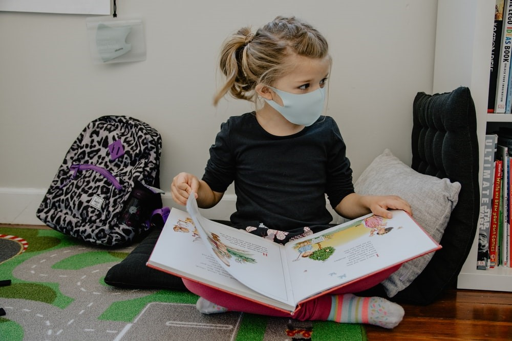 A girl wearing a mask and reading.