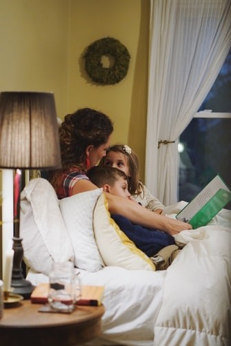 Mother reading a book with her children.