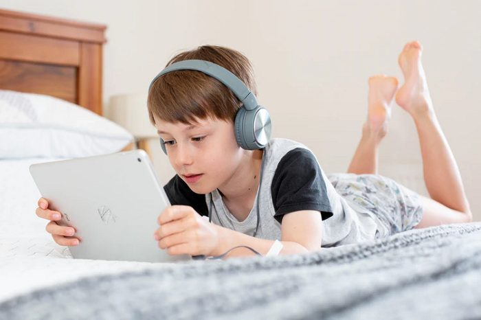 A boy listening to an Audiobook in bed