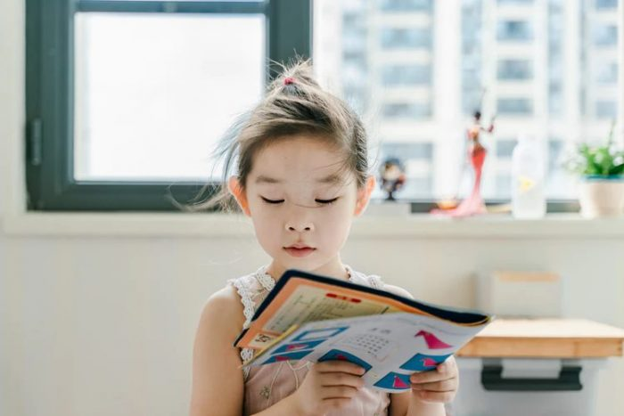 A young child reading a physical book